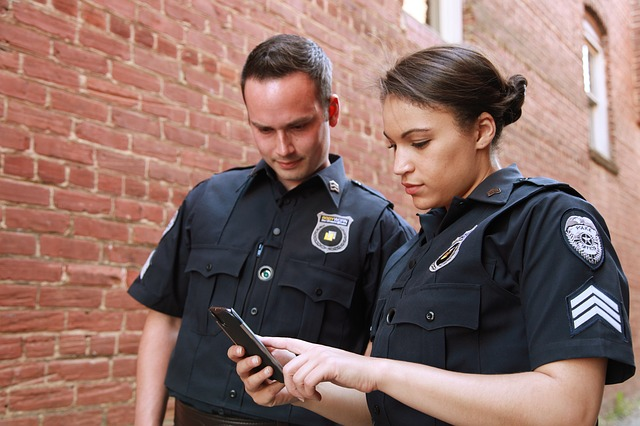two police officers looking at the cellphone