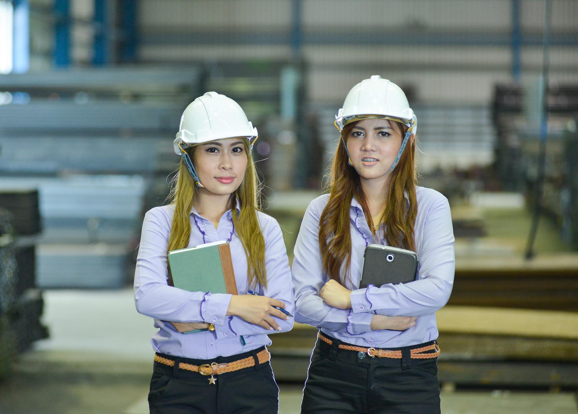 2 woman wearing a construction helmet