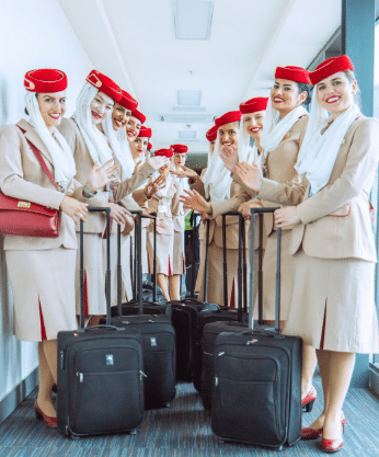 flight attendants wearing red hat and holding black luggage bag