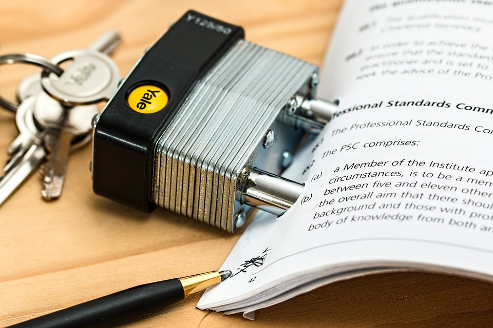 padlock with keys beside papers